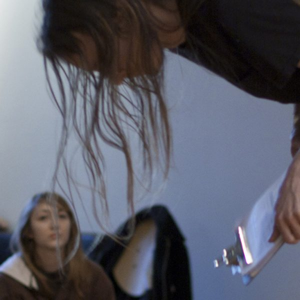 A performance artist with long hair bows in front of a group of seated spectators.